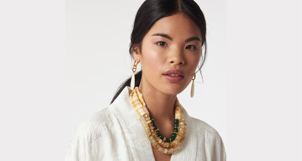 Two images of model wearing Picnic Necklace. The perfect blend of substance and whimsy, you'll stun in the citrine, green agate, and gold bead triple-strand statement necklace. Seal the deal with the yellow and white plaid silk taffeta tie.