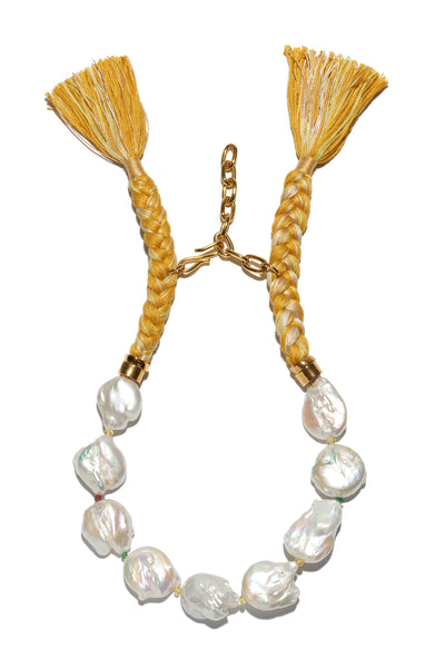 Thumbnail of Corsica Collar In Sunshine. Beach, office, opera - where can't you wear this pearl collar necklace? An updated take on the classic with marigold hand-braided tassel closure.