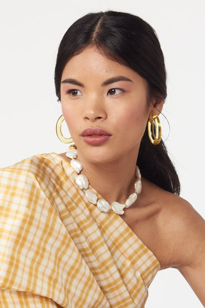 Thumbnail of model wearing Corsica Collar In Sunshine. Beach, office, opera - where can't you wear this pearl collar necklace? An updated take on the classic with marigold hand-braided tassel closure.