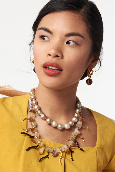"Thumbnail of model wearing Lightning Necklace. You'll be a lightning rod for compliments in the chalcedony and citrine beaded necklace with alternating gold and black enameled ""branch coral"" pendants. Want to make an even bigger statement? Layer it with the Corsica Collar as seen on our model."