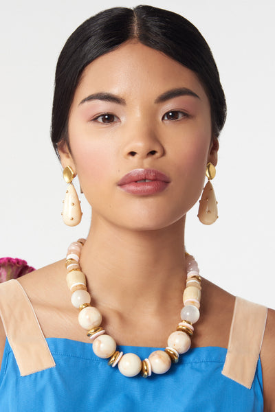Thumbnail of model wearing Quarry Necklace. Our latest take on the sophisticated single-strand necklace, in lucite, morganite, quartz, conch and gold-plated beads. We love that this palette of soft neutrals will work with any pop of color in your closet.