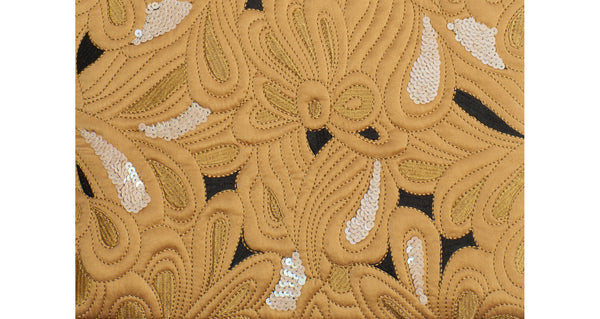 Close-up of Safari Clutch In Quilted Floral. This yellow quilted statement purse is brimming with unique details, from the hand-embroidery and pops of sequin, to the gingham and smooth black leather back, to the unexpected beaded strap. We can't wait for you to see this one up close.