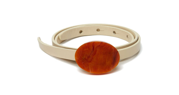 Full view of Orbit Belt In Cream And Terra Cotta. We don't like to play favorites, but this is one accessory we can't wait to wear with everything. Adjustable, skinny cream leather belt with gold-plated and terra cotta-colored acrylic oval buckle.