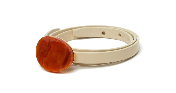Close-up view of Orbit Belt In Cream And Terra Cotta. We don't like to play favorites, but this is one accessory we can't wait to wear with everything. Adjustable, skinny cream leather belt with gold-plated and terra cotta-colored acrylic oval buckle.