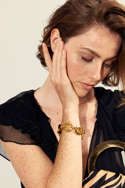 Thumbnail of model wearing the Elba Bracelet. Game, set, match. We love a classic, chunky tennis bracelet to serve a serious style upgrade to your arm party. In gold-plated brass linked discs.