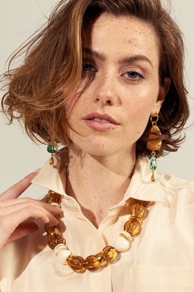 Thumbnail of model wearing the Waterfall Earrings. DO go chasing waterfalls, if it means donning our beautiful organic-shaped column earrings. With acrylic tangerine and transparent mineral green beads punctuated by delicate gold-plated drops, this pair is sure to get a lot of love.