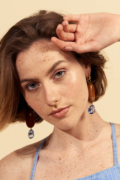 Thumbnail of model wearing the River Pebble Earrings. Inspired by the organic shapes of river rocks, these gold-plated linked earrings offer up stone cold style. Featuring caramel-colored acrylic nuggets inset with faceted semiprecious blue topaz and finished with transparent blue drop beads.
