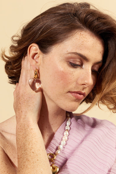 Thumbnail of model wearing the Cloud Nine Earrings. Who wouldn't feel heavenly in the most perfect pair of gold-plated hoop earrings with oversized (removable!) crystal heart charms?  We predict these will be the gift of the season.