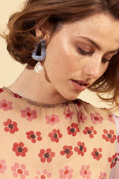 Thumbnail of model wearing the Blue Oasis Earrings. Dip your toes into very glamorous waters with our iridescent periwinkle, hand-embroidered beaded triangle earrings with hanging freshwater pearl drops. Pairs well with neutrals (think a classic camel coat) and peppy prints alike (as seen on our lovely model).
