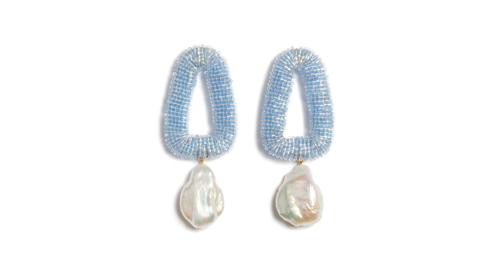 Full view of Blue Oasis Earrings. Dip your toes into very glamorous waters with our iridescent periwinkle, hand-embroidered beaded triangle earrings with hanging freshwater pearl drops. Pairs well with neutrals (think a classic camel coat) and peppy prints alike (as seen on our lovely model).