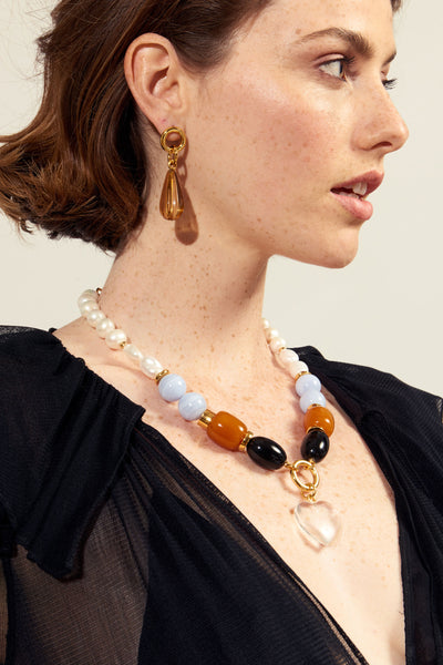 Thumbnail of model wearing the Desert Teardrop Earrings. Bring some warmth to your wardrobe in the gold-plated link earrings with fluted, peach-colored acrylic teardrops. This pair is truly, truly flattering.