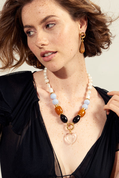 Thumbnail of model wearing the Cloud Nine Necklace. Make a statement in a classic single-strand bead necklace with a fresh color combination and luxe mixed materials. With freshwater pearls, blue lace agate, faux amber, and acrylic beads and the sweetest clear crystal heart pendant.