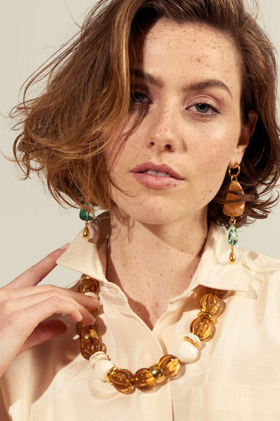 Thumbnail of model wearing the Candy Necklace In Amber. We can't get enough of this chunky, sophisticated confection of a necklace. With amber-colored fluted acrylic beads, gold-plated and bone beads, and freshwater pearl details.