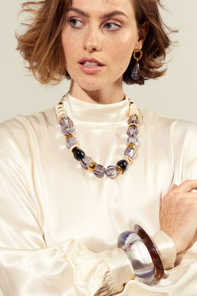 Thumbnail of model wearing the Candy Necklace In Lavender. We can't get enough of this chunky, sophisticated confection of a necklace. With lavender-colored fluted acrylic beads, gold-plated and bone beads, and freshwater pearl details.