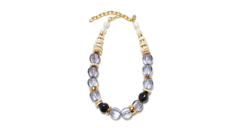 Full view of Candy Necklace In Lavender. We can't get enough of this chunky, sophisticated confection of a necklace. With lavender-colored fluted acrylic beads, gold-plated and bone beads, and freshwater pearl details.