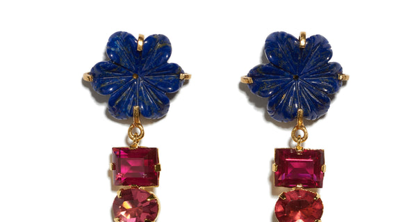 Top detail of Baroque Flower Earrings. Gold-plated brass and carved lapis flowers with dark pink cut glass stones and hanging lapis drops. Add an elegant and unique pop of color to any outfit.
