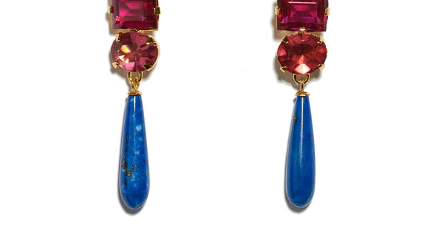 Bottom detail of Baroque Flower Earrings. Gold-plated brass and carved lapis flowers with dark pink cut glass stones and hanging lapis drops. Add an elegant and unique pop of color to any outfit.