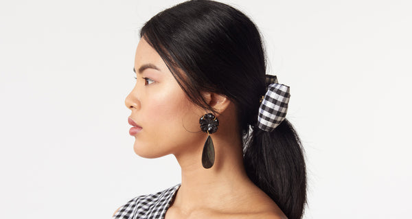 Model wearing the Night Bloom Earrings. Day or night, these classic earrings will be surefire stunners. Black agate flowers with long black abalone shell drops.