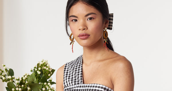 "Model wearing the Ornament Earrings. The season's most playful and unique statement-makers, for those who like to stand out in a crowd. Gold-plated brass and amber glass-beaded hoop earrings with vintage glass stones, red enameled ""branch coral"" casting and mother-of-pearl tops."