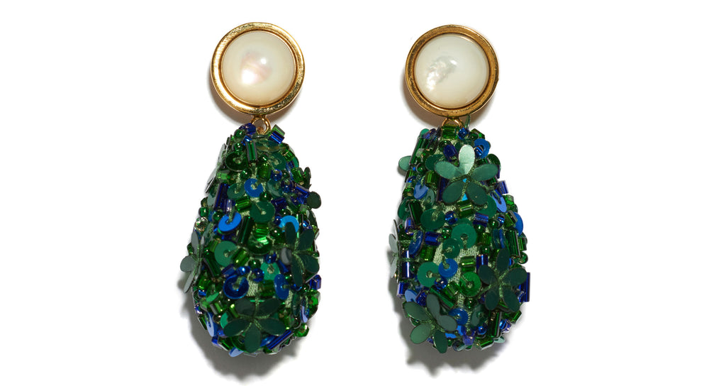 Close-up of Roman Party Earrings In Emerald. Make every day a party! These earrings are excellent for all occasions. In gold-plated brass with swinging blue and green sequin beaded teardrops and mother-of-pearl stone tops.