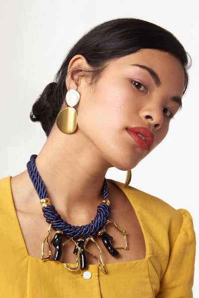 Thumbnail of model wearing the Painted Disco Earrings. We predict these will be your most versatile statement earrings - they truly go with everything. Gold-plated brass double discs with white painted enamel tops.