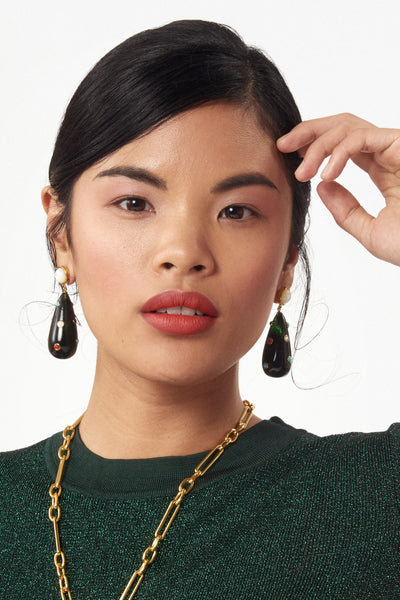 Thumbnail of model wearing the Prism Earrings In Rainbow. Shine bright in these subtle multicolor statement-makers. Dark acrylic drop earrings with assorted turquoise, pearl, red aventurine and pink tourmaline stone cabochons and mother-of-pearl tops.