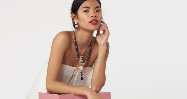 Model wearing the Fresco Earrings In Colour Block. A little simplicity goes a long way in these gold-plated brass earrings featuring pink opal, green quartz and dumortierite semiprecious square drops and mother-of-pearl tops.
