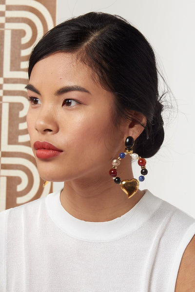 Thumbnail of model wearing the Candy Heart Earrings. Mixed-media pearl, glass and sodalite beaded hoop earrings with gold-plated heart charms and black agate stone tops. A colorful statement earring that's surprisingly easy to wear.