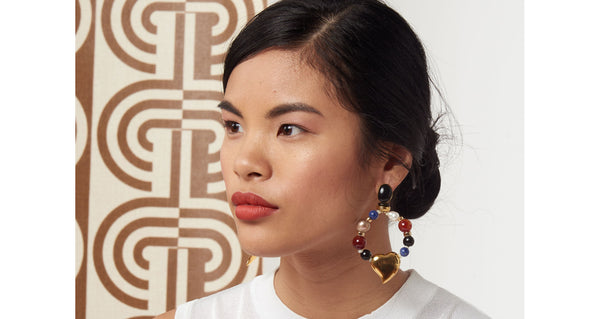 Model wearing the Candy Heart Earrings. Mixed-media pearl, glass and sodalite beaded hoop earrings with gold-plated heart charms and black agate stone tops. A colorful statement earring that's surprisingly easy to wear.