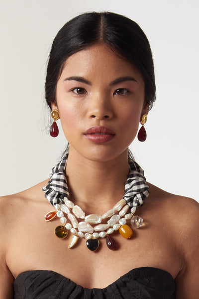 "Thumbnail of model wearing the Gourd Earrings. Gold-plated brass cast ""coin"" tops with hanging carved dark red bead drops. Big drama in a small earring."