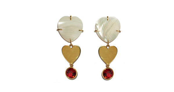 Full view of Ace Of Hearts Earrings. Mother-of-pearl hearts with gold-plated heart and red faceted glass hanging charms. Dainty and whimsical earrings suitable for everyday wear.