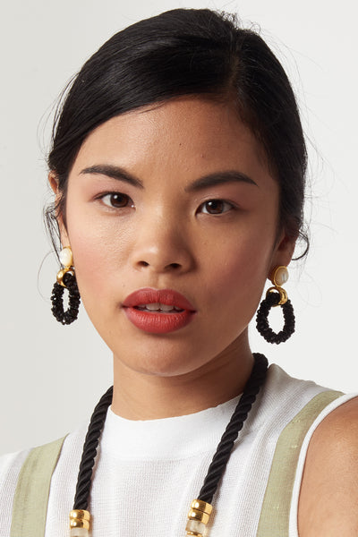 Thumbnail of model wearing the Brancusi Hoops In Black. These gold-plated brass and black cut glass beaded earrings with mother-of-pearl tops are a modern sculptural update on the classic hoop silhouette.