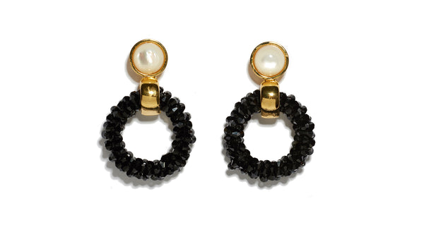Full view of Brancusi Hoops In Black. These gold-plated brass and black cut glass beaded earrings with mother-of-pearl tops are a modern sculptural update on the classic hoop silhouette.