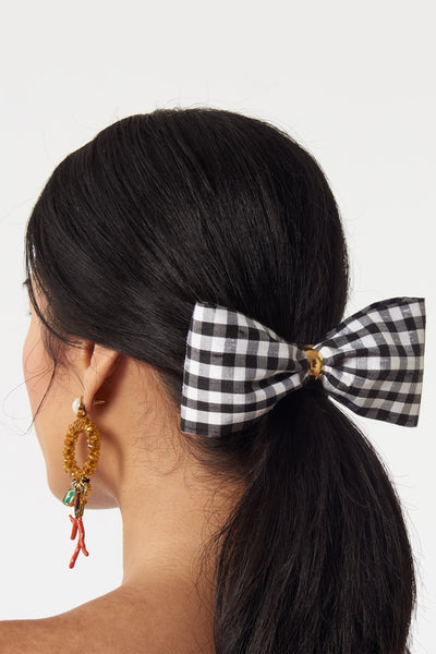 Thumbnail of model wearing the Bow In Gingham. The sweetest way to raise the style profile of your everyday ponytail is with our new barrette with black and white gingham silk shantung bow.