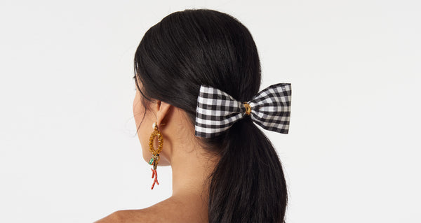 Model wearing the Bow In Gingham. The sweetest way to raise the style profile of your everyday ponytail is with our new barrette with black and white gingham silk shantung bow.