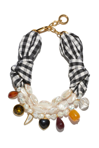 Thumbnail of Carolina Necklace. This black and white gingham silk and freshwater pearl statement necklace is a mixed-medium piece that begs for compliments. Featuring carnelian, black agate, mother-of-pearl, faceted glass and acrylic charms.