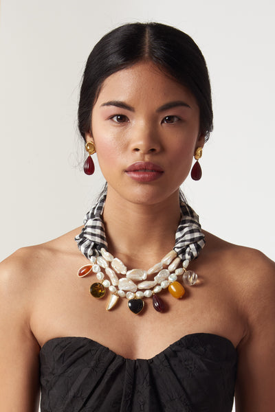 Thumbnail of model wearing the Carolina Necklace. This black and white gingham silk and freshwater pearl statement necklace is a mixed-medium piece that begs for compliments. Featuring carnelian, black agate, mother-of-pearl, faceted glass and acrylic charms.