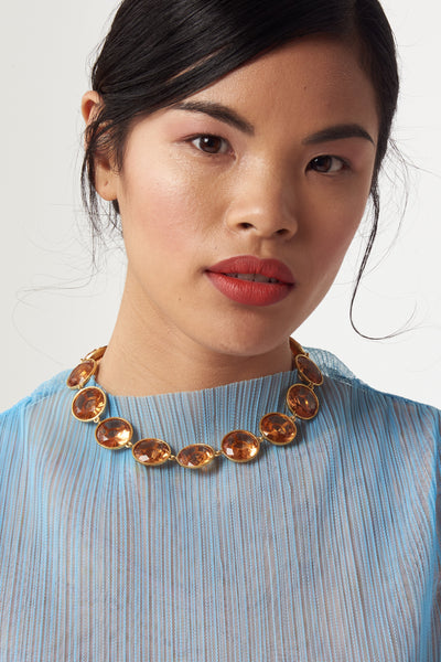 Thumbnail of Anna Collar necklace as worn by model. Gold-plated brass and champagne-colored faceted glass linked collar with black agate flower closure. Special and classic.