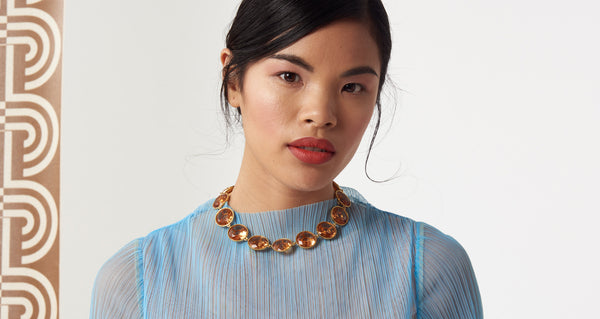 Model wearing the Anna Collar necklace. Gold-plated brass and champagne-colored faceted glass linked collar with black agate flower closure. Special and classic.