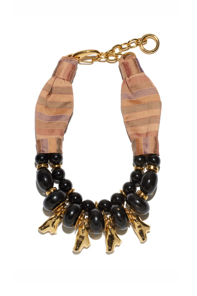 Thumbnail of Caravan Necklace. Our newest necklace silhouette merges a rich assortment of materials for a mixed-medium statement piece that begs for compliments. Striped silk fabric and black onyx and acrylic beaded necklace with gold-plated coral-shaped charms.