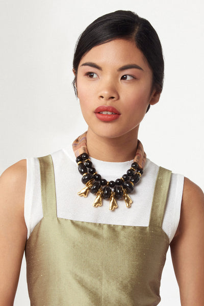 Thumbnail of model wearing the Caravan Necklace. Our newest necklace silhouette merges a rich assortment of materials for a mixed-medium statement piece that begs for compliments. Striped silk fabric and black onyx and acrylic beaded necklace with gold-plated coral-shaped charms.