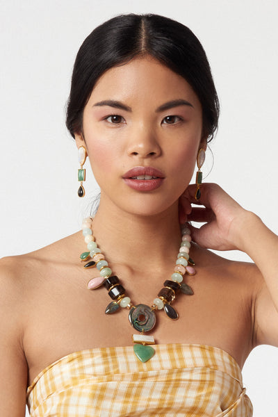 Thumbnail of model wearing What's Old Is New Necklace. Prepare yourself for compliments; this mixed material necklace is a true showstopper. Light aqua and pink morganite, quartz and gold-plated beads with pink opal, black agate, labradorite, jade, green quartz and obsidian semiprecious charms with abalone shell, mother-of-pearl and green quartz heart pendant.