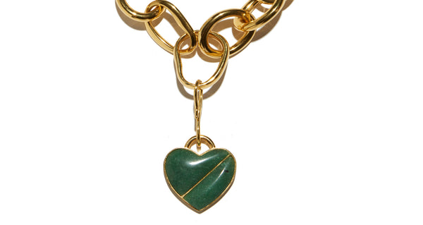 Pendant detail of Porto Necklace In Green Heart.  With its large links and detachable heart pendant, the Porto Necklace makes for a perfect subtle statement. Gold-plated brass chain with green quartz semiprecious stone heart.