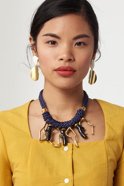 Thumbnail of model wearing the Mariner Necklace. Get yourself wrapped up in a statement-making nautical-inspired twist with the navy cord necklace, featuring hanging gold-plated and acrylic abstract coral-shaped charms.