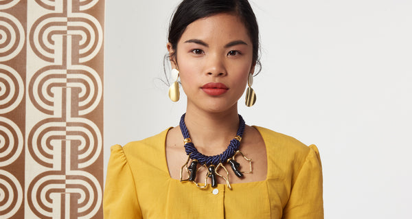 Model wearing the Mariner Necklace. Get yourself wrapped up in a statement-making nautical-inspired twist with the navy cord necklace, featuring hanging gold-plated and acrylic abstract coral-shaped charms.