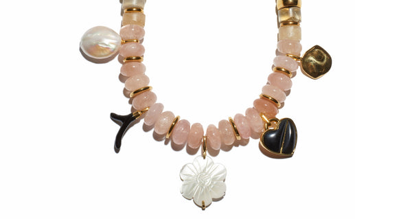 Bottom charm detail of Memento Necklace. Quite possibly the prettiest way to make a statement. Adjustable twist cord and light pink morganite beaded necklace with pearl, black agate, enameled and gold-plated heart and flower charms.