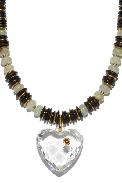 Thumbnail close-up of Modern Love Necklace. It's just the power to charm. Black coconut heishi, prehnite and gold-plated brass beaded necklace with large, faceted acrylic heart pendant with garnet cabochon detail.