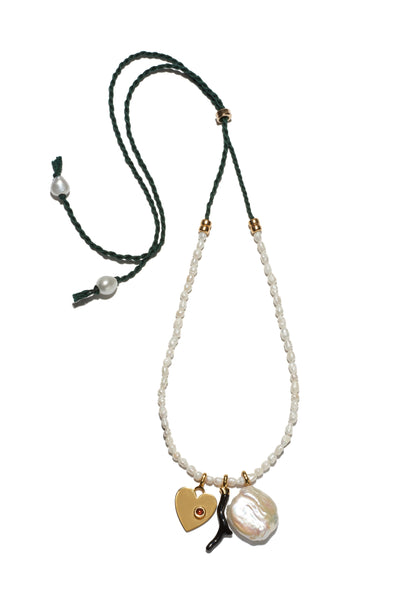 Thumbnail of Uptown Charm Necklace. A fresh medley of pearls and assorted charms come together in an adjustable layering piece you will want to show off every day. Small rice pearl beaded necklace with assorted freshwater pearl, brass, garnet, and enameled charms with cord back.