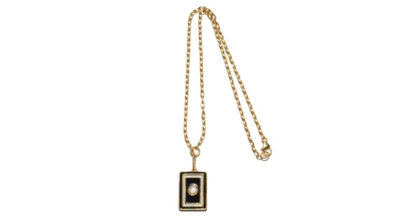 "Full view of Tarot Necklace In Black And White. A wear-everyday layering piece with an heirloom feel. Your good fortune is assured with the gold-plated vermeil chain necklace and brass ""frame"" pendant in black and white enamel and mother-of-pearl cabochon."