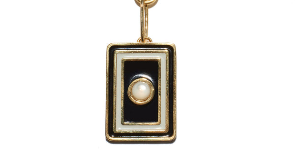 "Close-up of pendant in Tarot Necklace In Black And White. A wear-everyday layering piece with an heirloom feel. Your good fortune is assured with the gold-plated vermeil chain necklace and brass ""frame"" pendant in black and white enamel and mother-of-pearl cabochon."